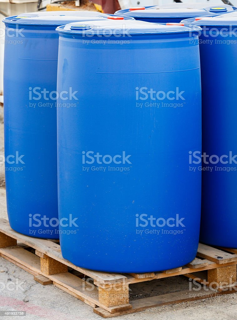 Blue plastic barrels on pallet stock photo