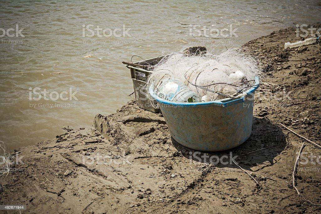 Blue plastic bucket is full of fishing net. stock photo