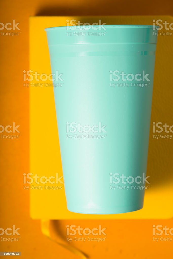 Blue plastic cup on the yellow background  vertical stock photo