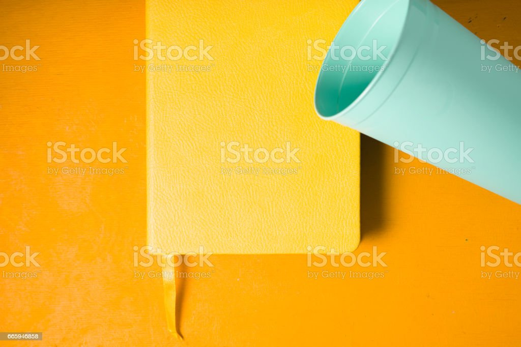 Blue plastic cup with notebook on yellow background top view stock photo