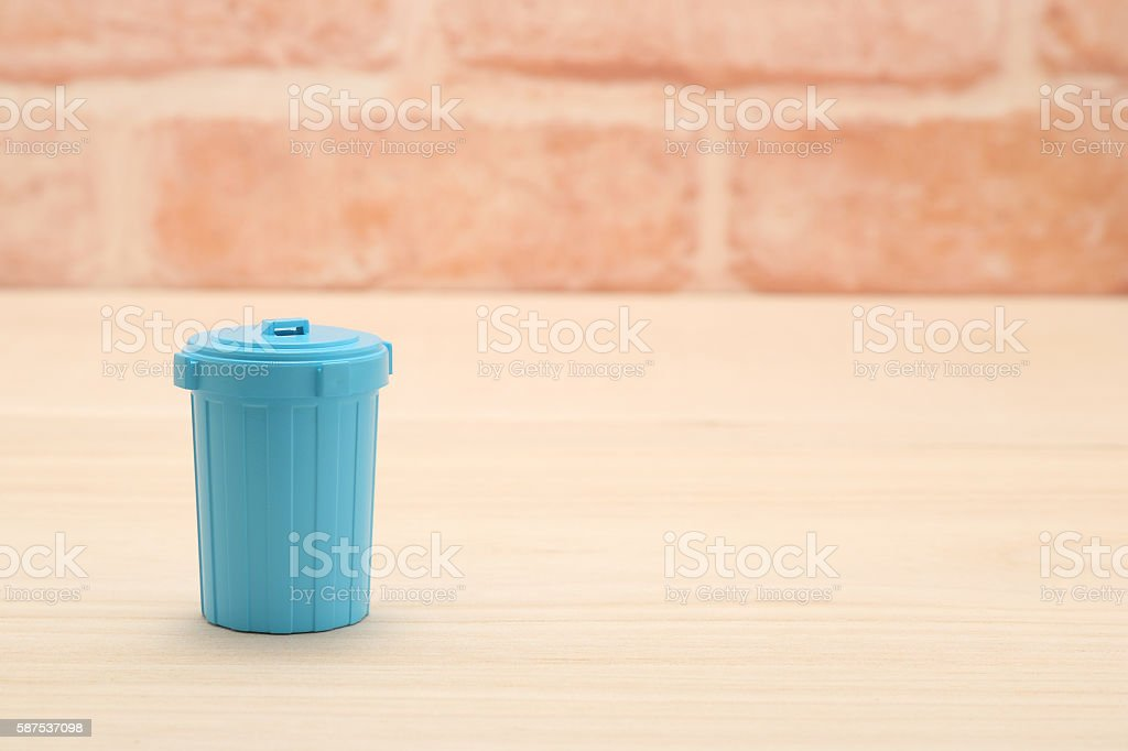 Blue plastic garbage bin in front of brick wall. stock photo