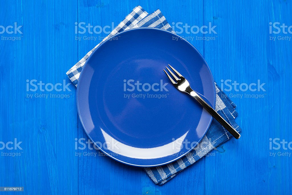 Blue plate, napkin and table, top view stock photo