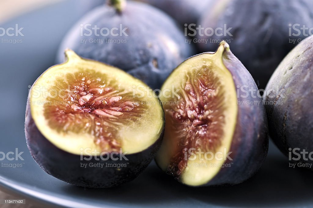Blue plate of sliced figs on a wooden table stock photo