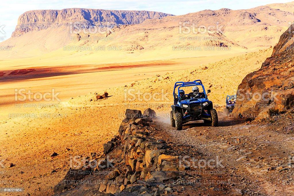 blue Polaris RZR 800 crossing  a mountain road stock photo