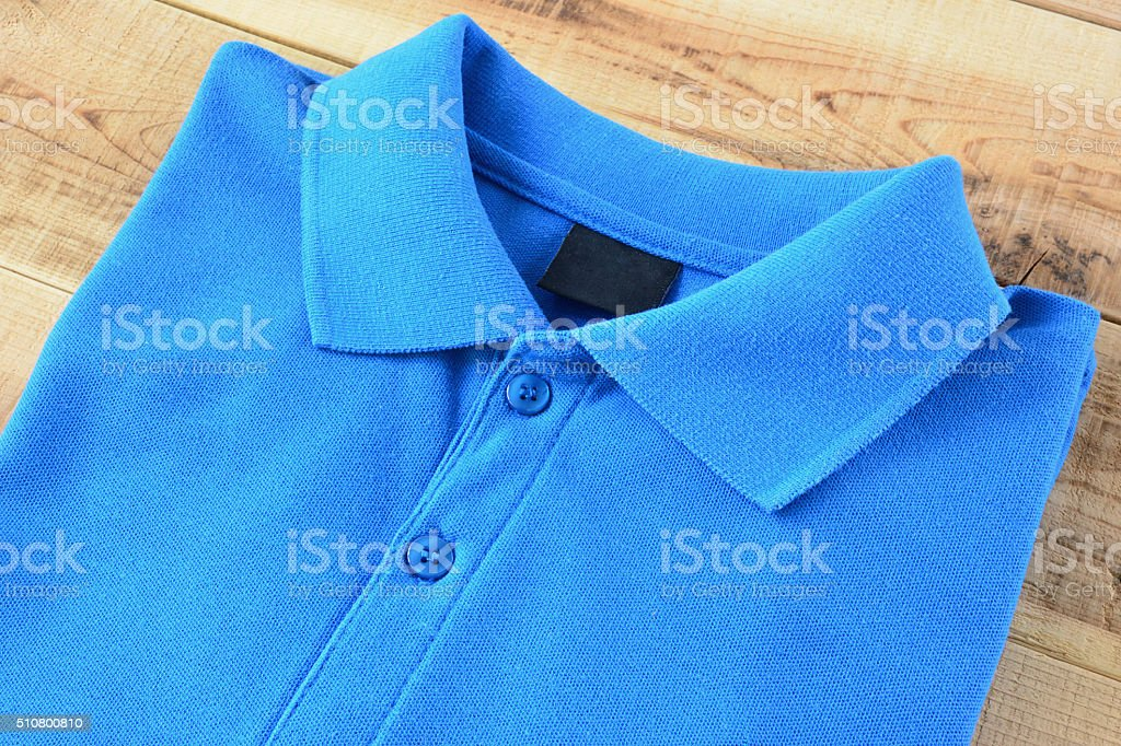 Blue Polo T-shirt on wooden. stock photo