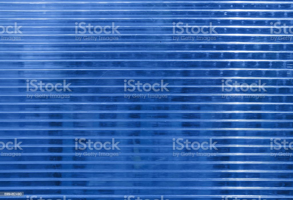 Blue polycarbonate surface with objects behind stock photo