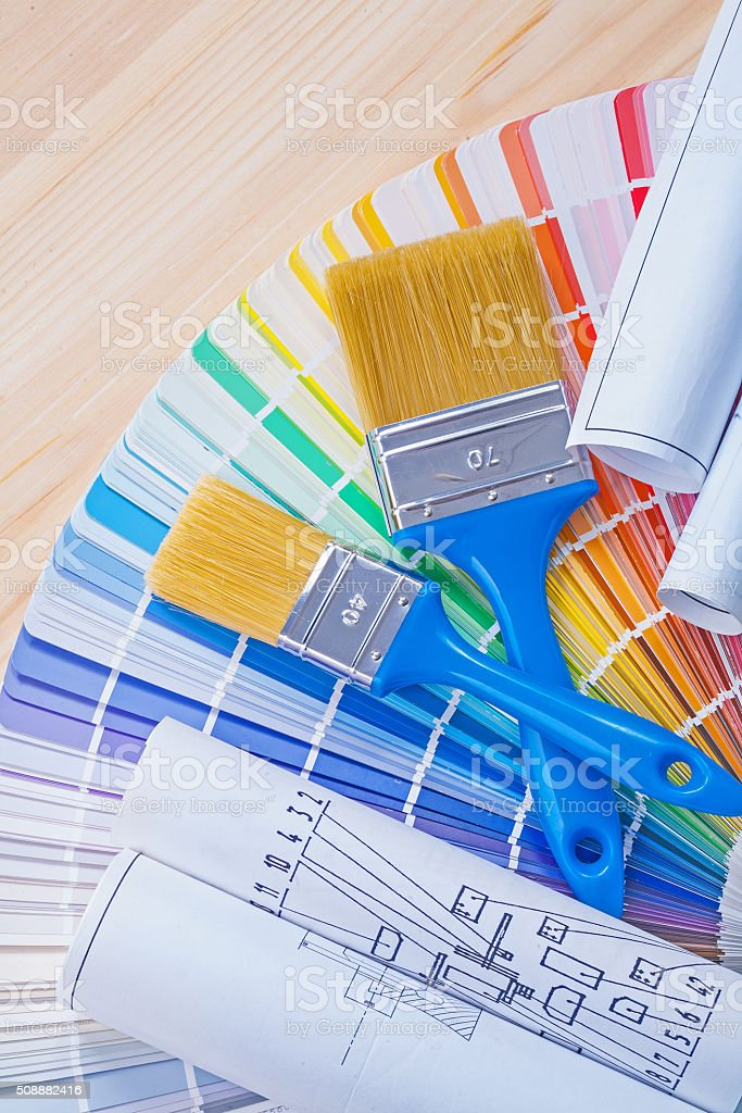 blue prints and paintbrushes on opened color palette stock photo