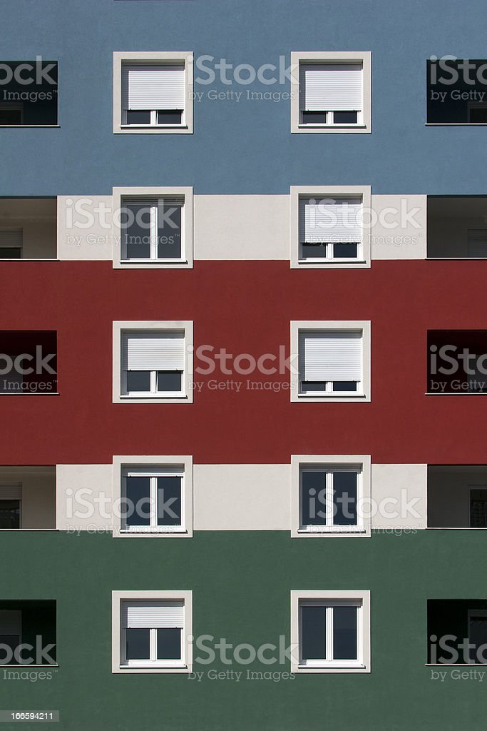 Blue, red and green facade with white windows royalty-free stock photo