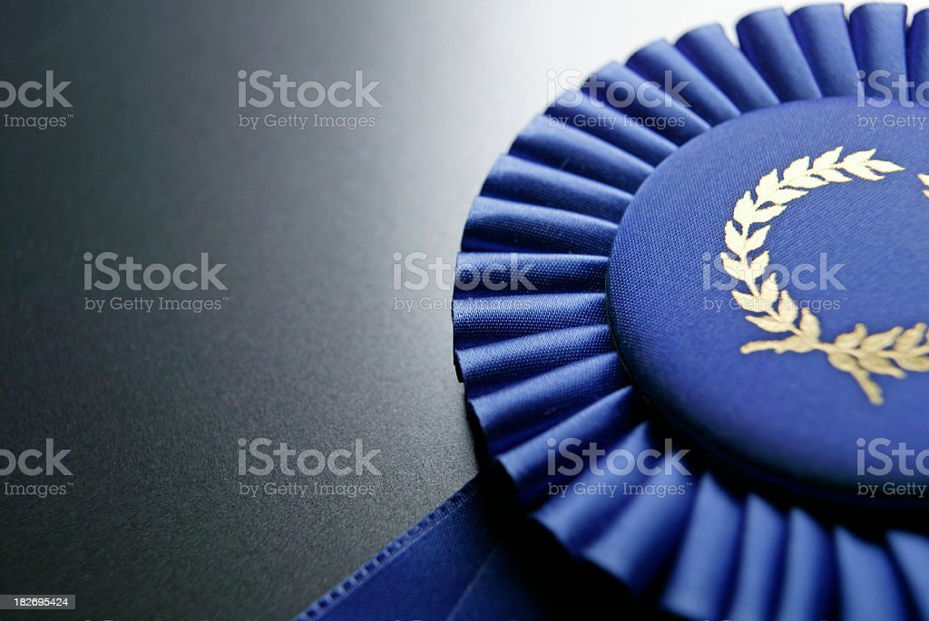 Blue ribbon rosette on dark gray graduated background stock photo