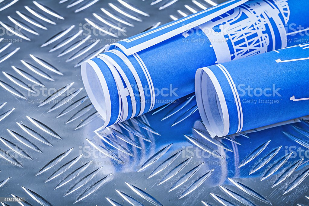 Blue rolled engineering drawings on corrugated metal background stock photo