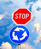 Blue roundabout crossroad road traffic sign with STOP sign against
