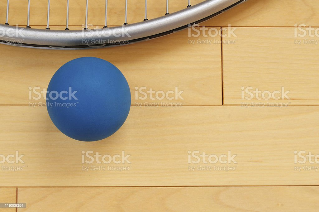 A blue rubber racquetball and racquet on a wooden floor stock photo