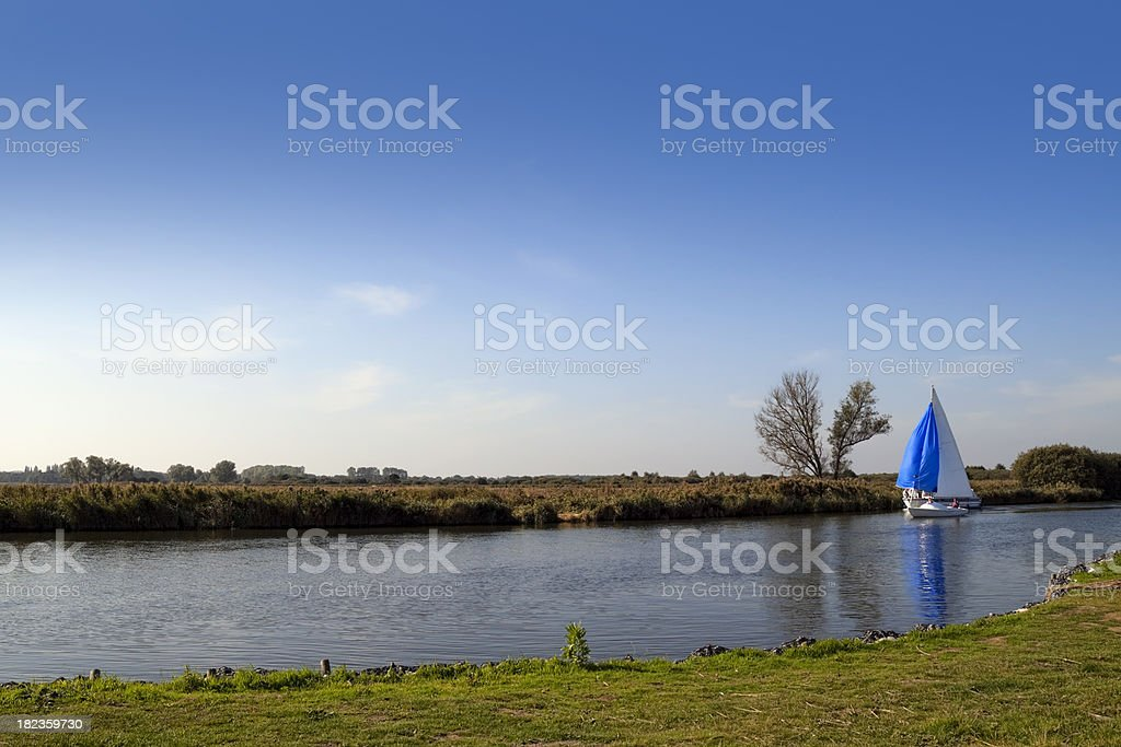 Blue sail on the River Bure stock photo