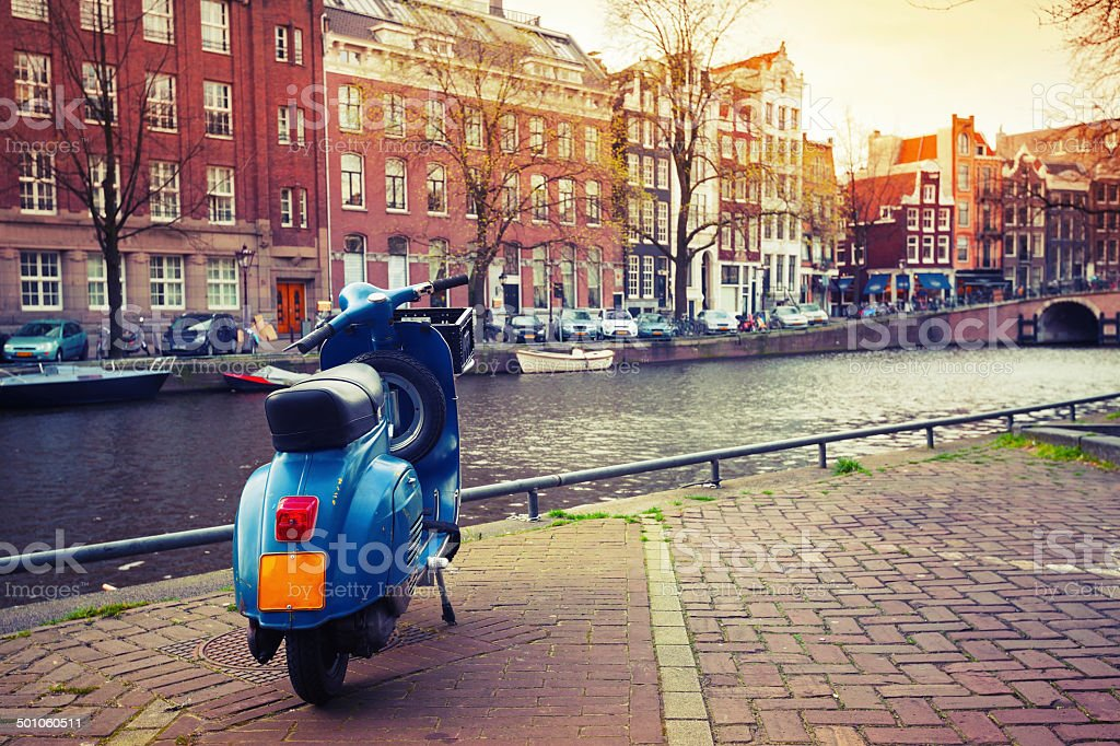 Blue scooter stands parked on the canal coast in Amsterdam stock photo