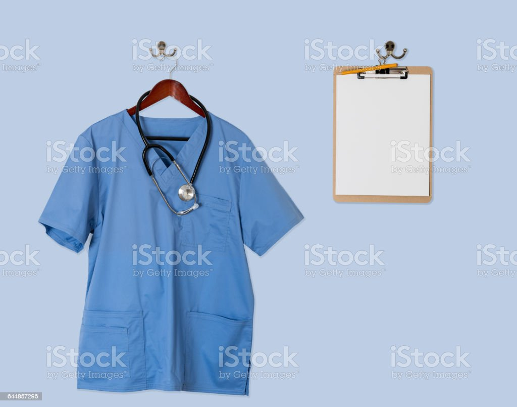Blue scrubs shirt for medical professional hanging on door stock photo