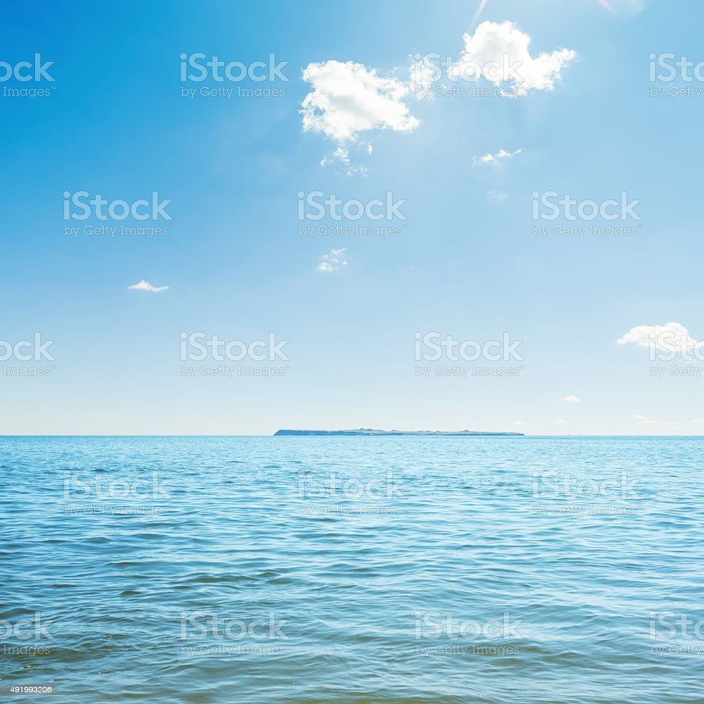 blue sea and clouds in sky. island on horizon stock photo