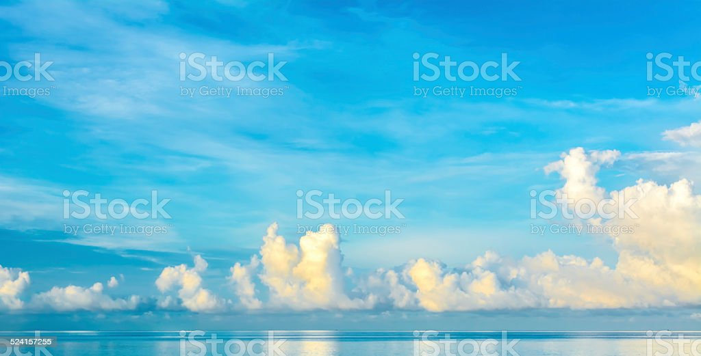blue sea and cloudy blue sky over it. stock photo