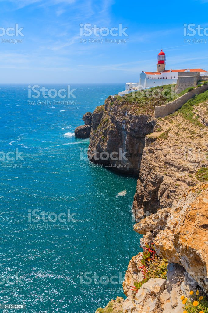 Blue sea and lighthouse on top of cliff at Cabo Sao Vicente, Algarve region, Portugal stock photo