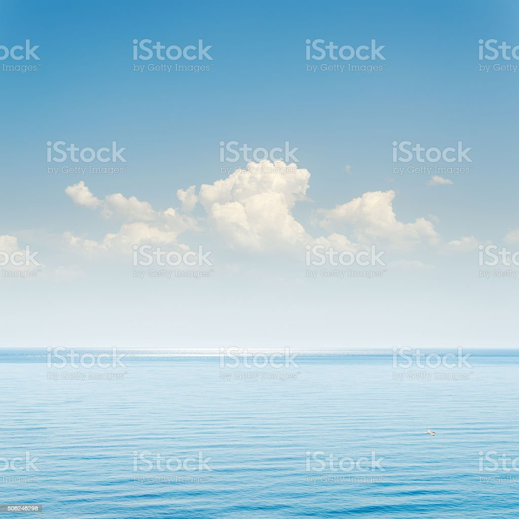 blue sea and sky with clouds over it stock photo