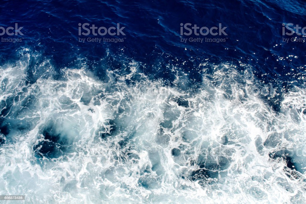 Blue sea waves with a lot of sea foam. Beautiful blue waves with a lot of sea foam scene looked from above, close up. stock photo