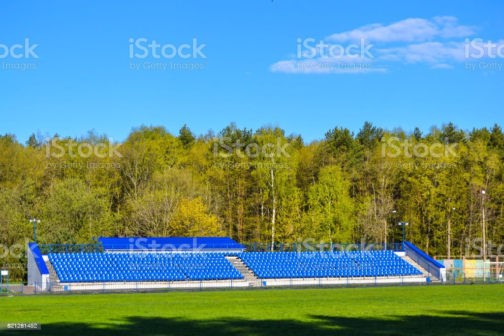 Blue seats on the tribune for fans in a stadium located in the forest zone stock photo