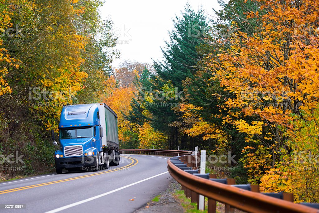 Blue semi truck on winding highway in autumn Columbia Gorge stock photo