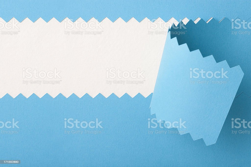 Blue serrated card reveals white textured paper stock photo