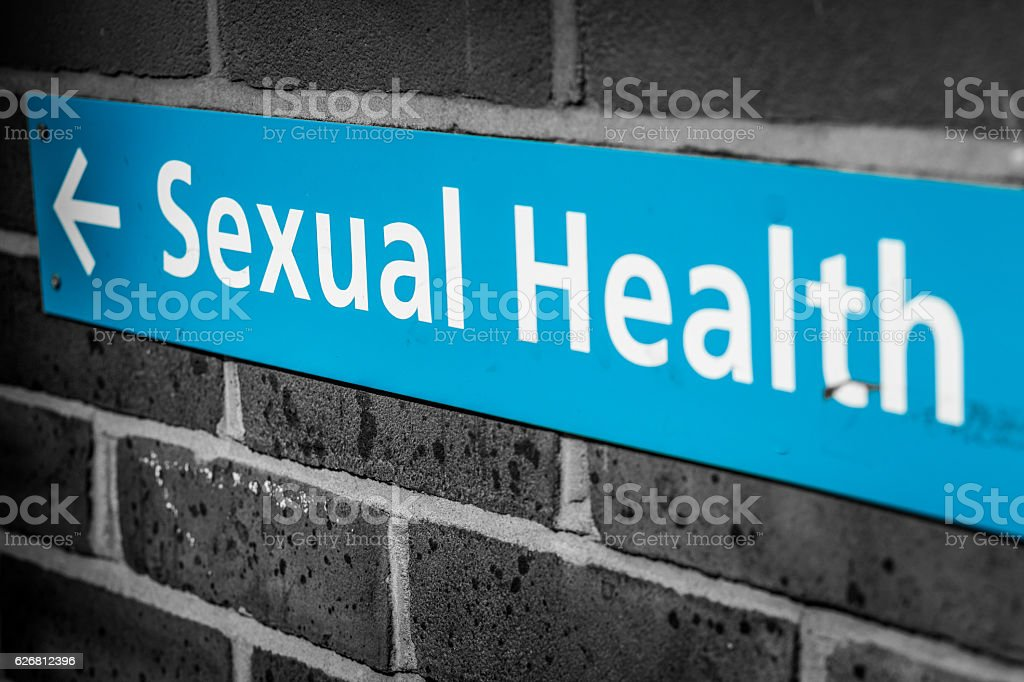 Blue sexual health sign with brick wall background stock photo