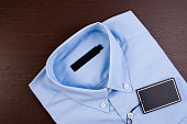 Blue shirt with black blank price tag.