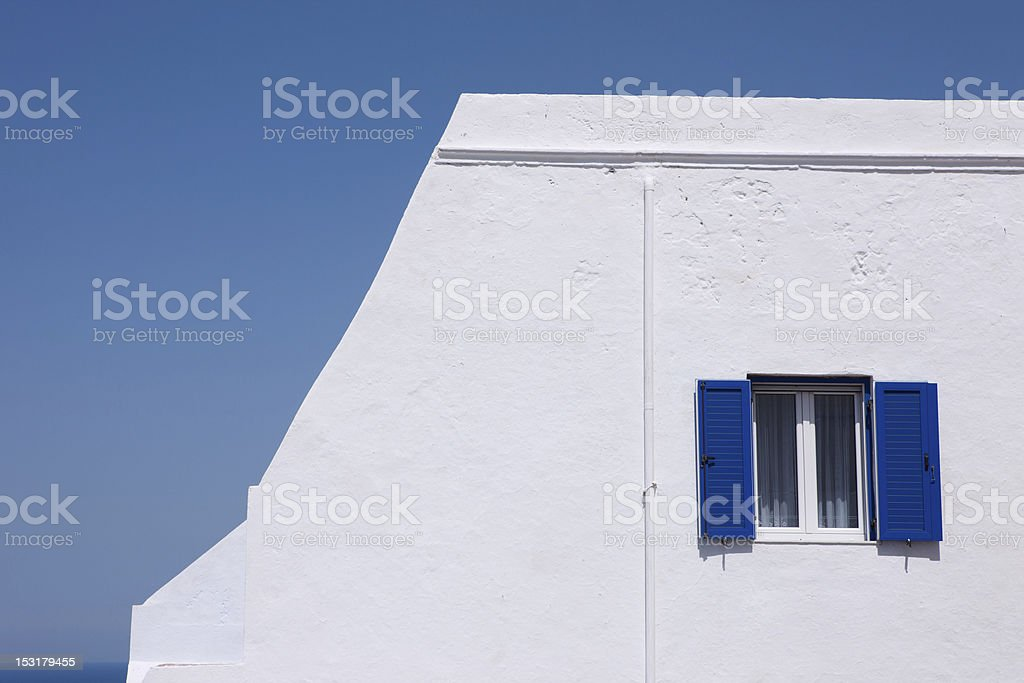 Blue shutters on white-washed wall royalty-free stock photo