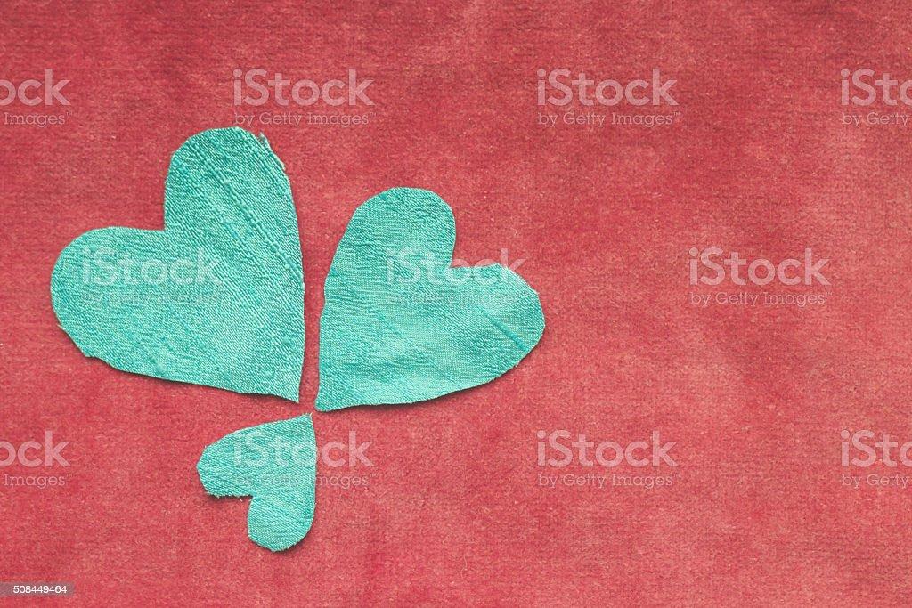 Blue silk hearts arranged in flower pattern on red velvet stock photo