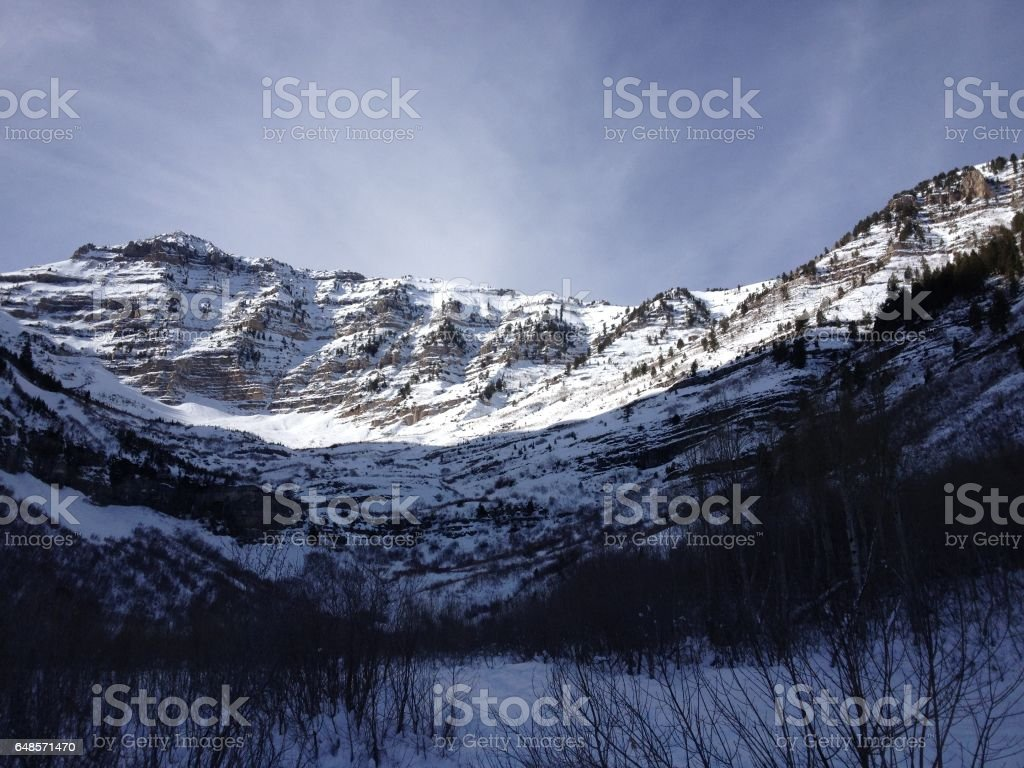 Blue skies and sun shines on the Wasatch Mountains covered with snow on a winter's day in Sundance, Utah. stock photo