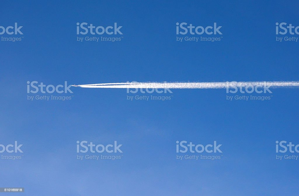 Blue Sky and Condensation Trail of an Airplane stock photo