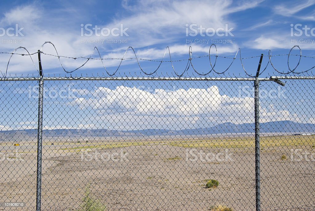 Blue Sky and Fluffy Clouds Behind Barb Wire Fence royalty-free stock photo