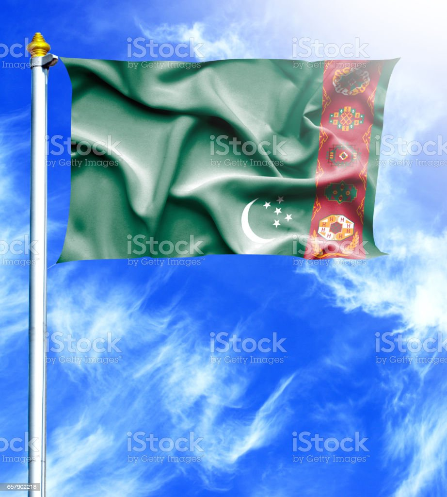 Blue sky and mast with hanged waving flag of Turkmenistan stock photo