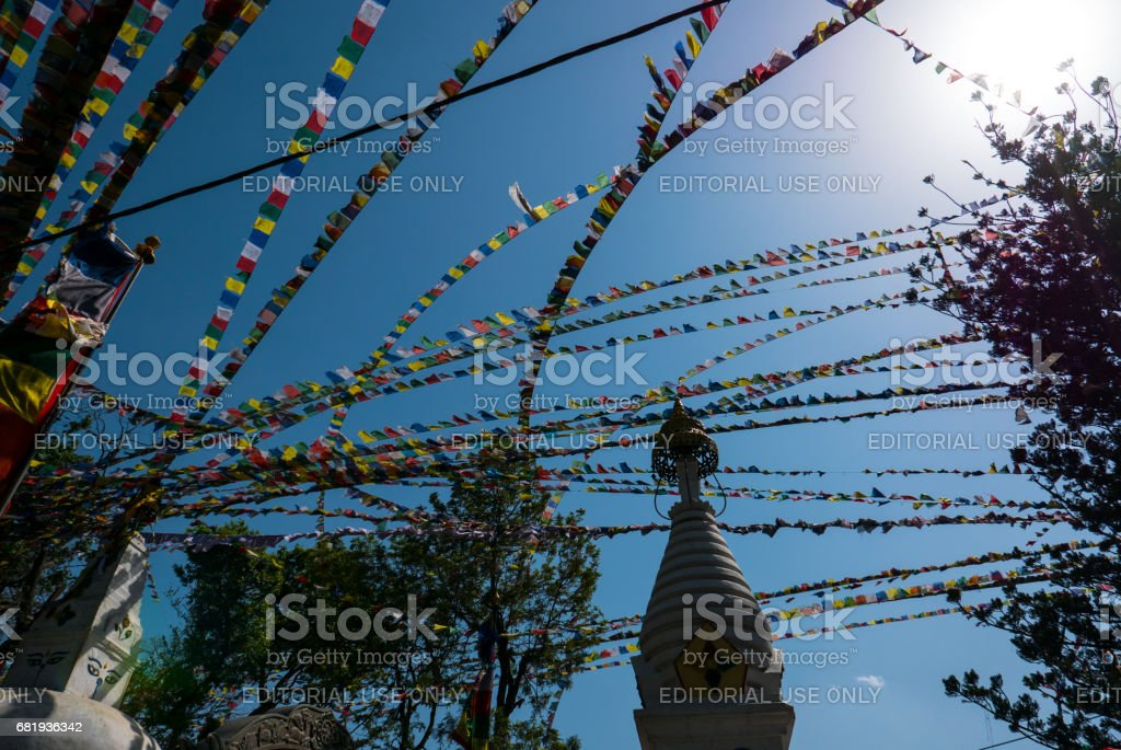 Blue sky and prayers flags between trees in Nepal stock photo