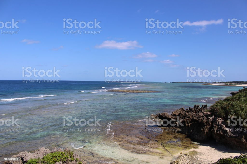 Blue sky and sea, There are big rocks in the beach beside the ocean, there is a bridge that connects the island across the ocean in Miyako island, Okinawa, Japan. stock photo