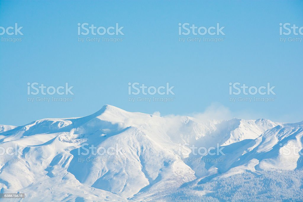 Blue sky and summit of winter mountain stock photo