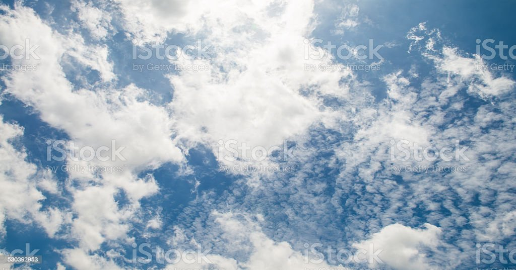 blue sky and white fluffy clouds stock photo