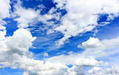 Blue sky background with clouds. Blue hues and outdoor.