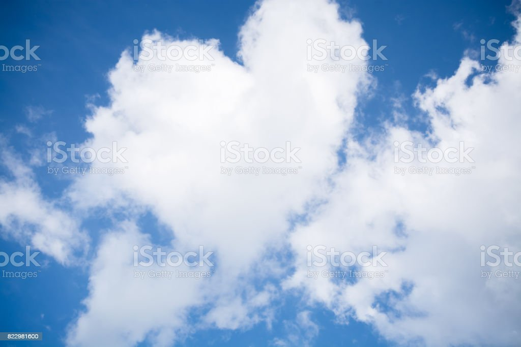 Blue sky background with white fluffy clouds stock photo