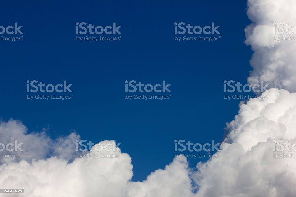 Blue sky framed with white cumulonimbus clouds stock photo