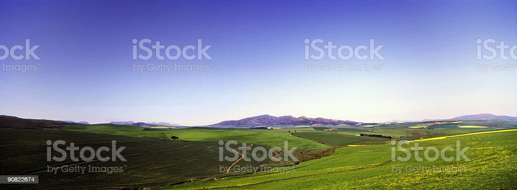 Blue sky green fields and mountains stock photo