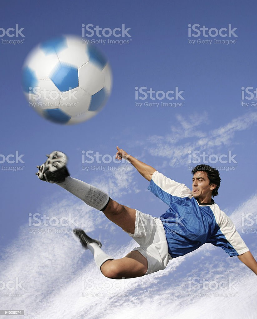 Blue sky over best soccer player hitting the ball royalty-free stock photo