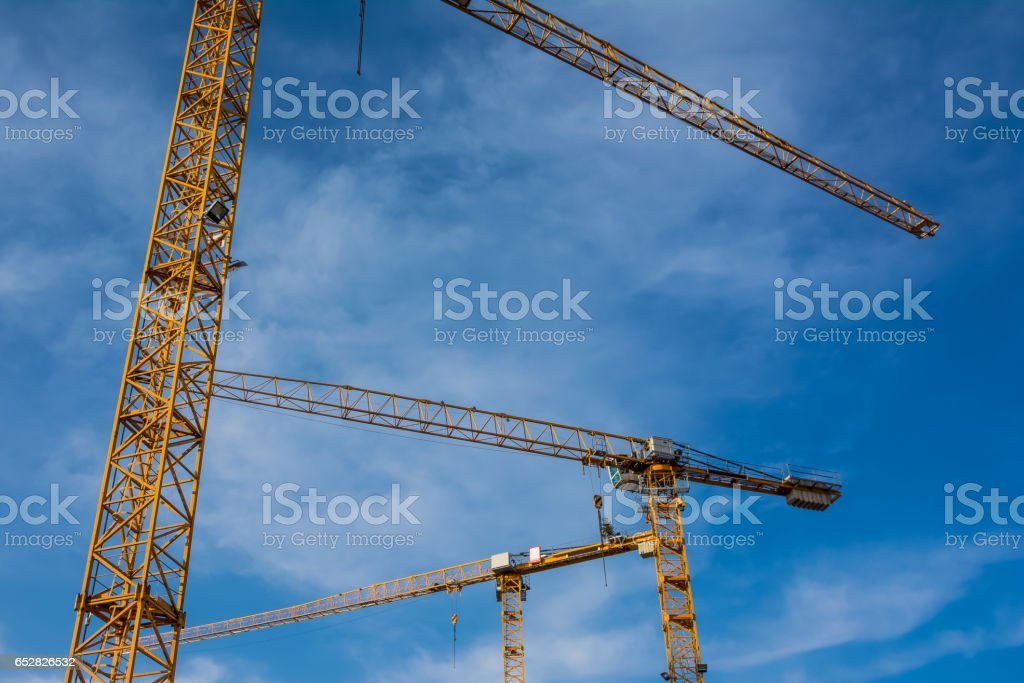Blue Sky Over Construction Cranes Yellow Diagonal Copyspace Building Architecture Working Operation Frame Metal stock photo