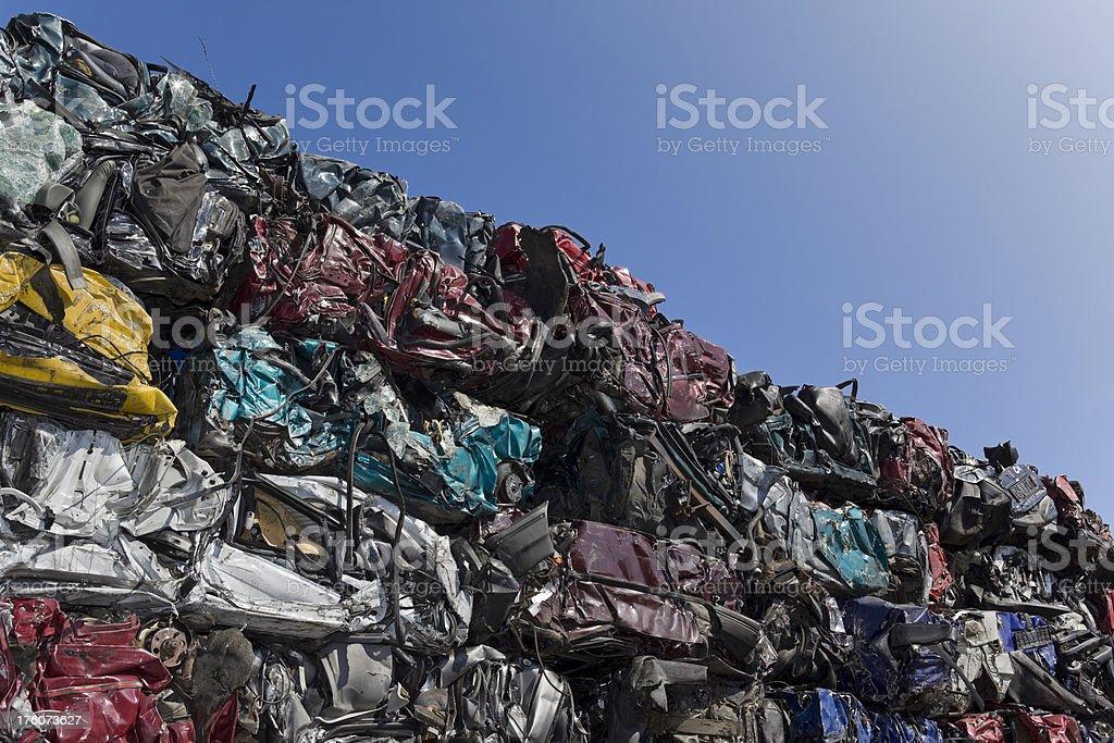 Blue sky over mountain of car wrecks royalty-free stock photo