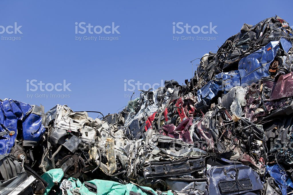 Blue sky over old greasy car parts on junkyard royalty-free stock photo