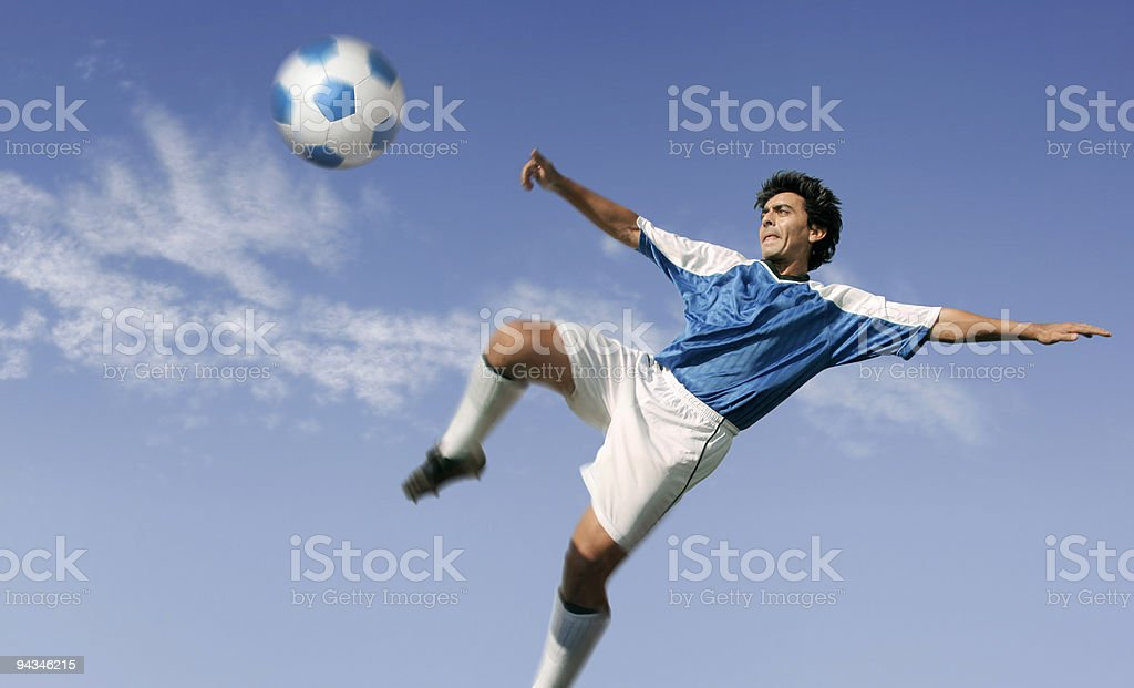 Blue sky over soccer player hitting ball royalty-free stock photo