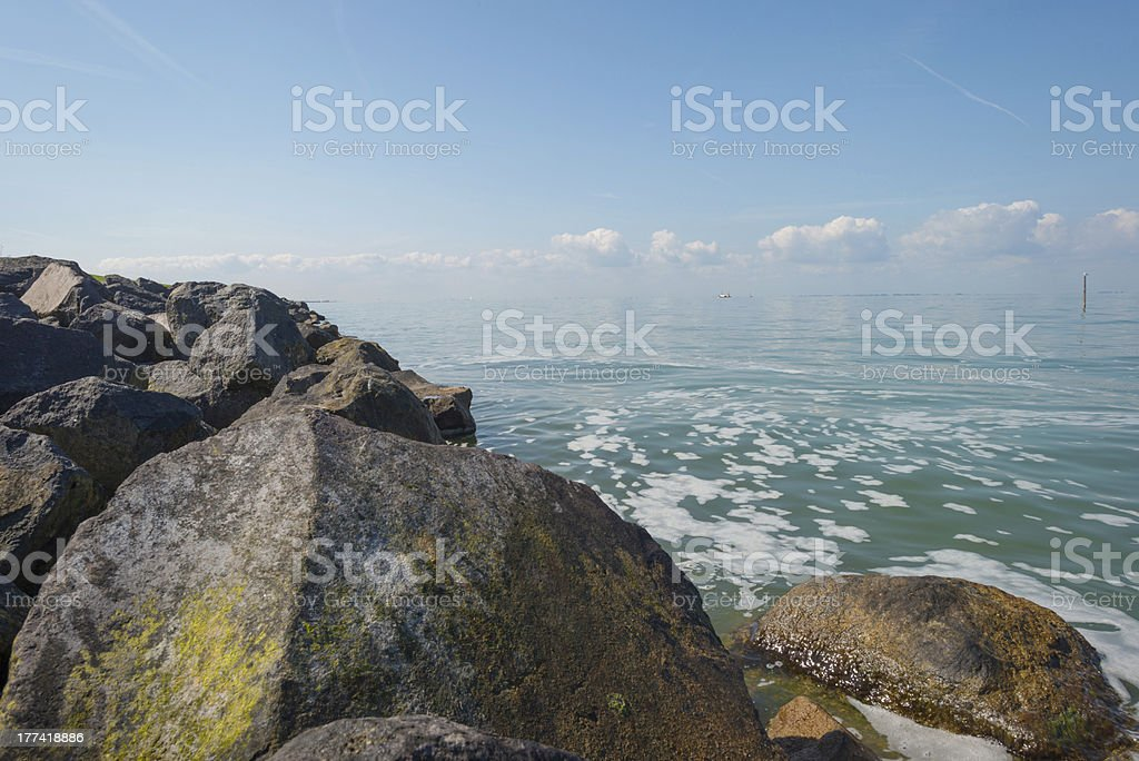 Blue sky over stones in a lake royalty-free stock photo