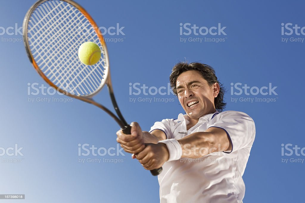Blue sky over tennis player hitting the ball stock photo